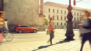 frederic-schlosser-sony-alpha-7R-orange-car-parked-in-town-square-as-onlookers-walk-past